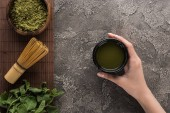 top view of woman holding matcha matcha tea on table with whisk, powder and mint