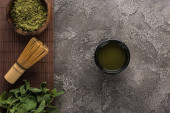 top view of green matcha tea on bamboo mat on dark stone table