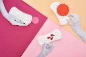 Papierschnitt weiße Hände mit weißen Damenservietten in der Nähe leerer Karten und Blutstropfen auf lila, rosa und beigem Hintergrund