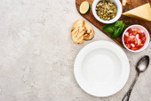 top view of empty plate near wooden cutting board with fresh ingredients