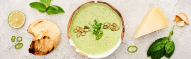 panoramic shot of tasty green creamy soup with croutons, cheese and spinach on textured grey background