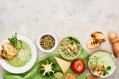Fotografie Top-Ansicht der köstlichen cremigen grünen Suppe mit Gemüse und Croutons auf grüne Serviette serviert