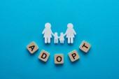 pohled na papír řezaných lesbických rodin držení rukou na modrém pozadí s adoptivním písmem na kostkách