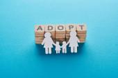 Papírová lesbická rodina držící ruce na modrém pozadí s adoptivním písmem na dřevěných kostkách