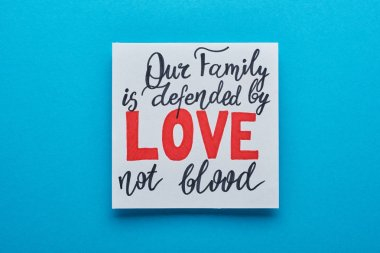 Top view of card with our family is defended by love not blood lettering on blue background stock vector