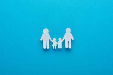 Top view of paper cut family holding hands on blue background stock vector