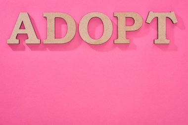 Top view of cardboard word adopt on pink background with copy space stock vector