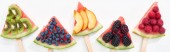 panoramic shot of fresh watermelon on sticks with seasonal berries and fruits on white background