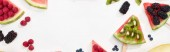 panoramic shot of delicious watermelon on sticks with berries and kiwi on white background