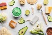 pohled na přírodní kosmetika, miniaplikace a mýdlo v blízkosti čerstvých květin, zeleniny a ovoce na povrchu mramoru