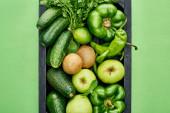 pohled na jablka, avokáda, okurky, papriky, kiwi, zeleň a cuketa v dřevěné krabici