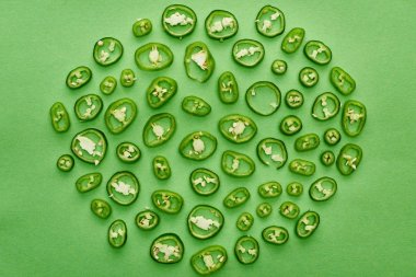 top view of sliced and fresh peppers on green background