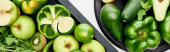 panoramic shot of avocados, peppers, kiwi, apples, limes and greenery on pizza skillet and box