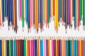 Řádky zaostřených barevných tužek izolovaných na bílém