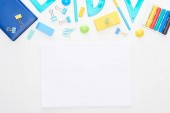 Photo Top view of blue and yellow scattered school supplies with notepads near clear paper isolated on white