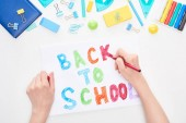 Cropped image of schoolgirl holding card with back to school lettering isolated on white