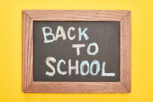 Chalkboard in wooden frame with back to school inscription on yellow background