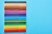 Pohled shora na sadu barevných per s plstěných pery izolovaných na modré