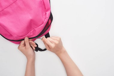 cropped view od schoolkid zipping bright pink schoolbag isolated on white