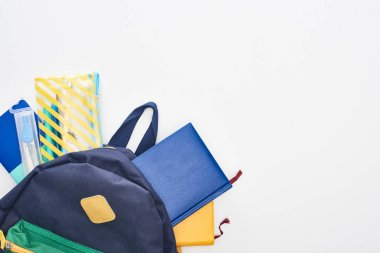 Blue schoolbag with notepads, pencil case and school supplies isolated on white