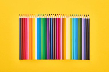 Panoramic shot of sharpened color pencils isolated on yellow stock vector