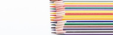 Panoramic shot of sharpened color pencils row on white stock vector
