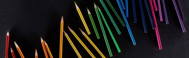 Panoramic shot of rainbow gradient made with sharpened color pencils isolated on black