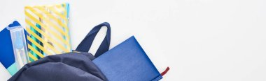 Panoramic shot of blue schoolbag with notepads, pencil case and school supplies isolated on white