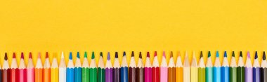 Panoramic shot of straight line of color pencils isolated on yellow stock vector