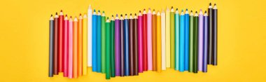 Panoramic shot of color pencils set isolated on yellow stock vector