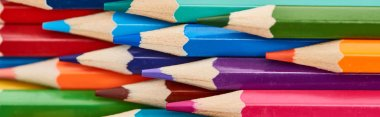 Panoramic shot of color wooden pencils with sharpened ends