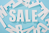 Photo top view of white sale lettering among letters on blue background