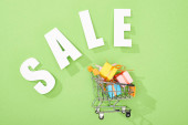 top view of decorative gift boxes in shopping cart near white sale lettering on green background