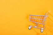 top view of empty shopping cart on bright orange background