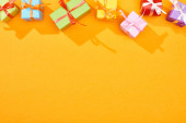 top view of festive wrapped gifts on bright orange background