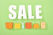 zobrazení dekorativních nákupních sáčků a bílých výprodejů na zeleném pozadí