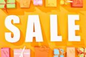 Nejlepší pohled na bílou prodeju v blízkosti nákupních tašek a dárků na světle oranžovém pozadí