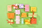 pohled na dekorativní dárkové krabice a nákupní tašky na zeleném pozadí