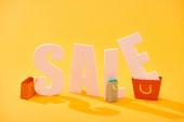 bílý prodej nápis poblíž nákupních tašek na světle oranžovém pozadí