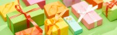 Photo selective focus of decorative colorful gift boxes on green background, panoramic shot