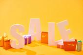 kis bevásárló táskák között fehér eladás betűkkel, narancssárga háttér
