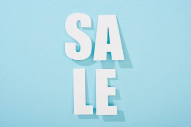 Top view of white sale lettering on blue background with copy space stock vector