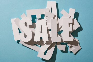 top view of white sale lettering on pile of letters on blue background