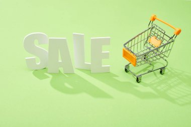 white sale lettering near decorative shopping cart on green background