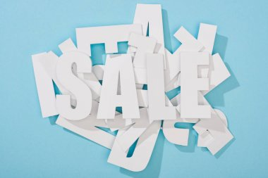 top view of white sale word on pile of letters on blue background
