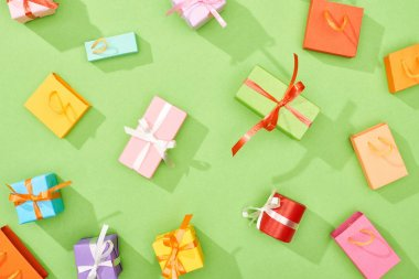 top view of scattered gift boxes and shopping bags on green background