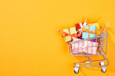 top view of shopping cart with presents on bright orange background