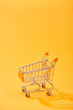 empty small shopping cart on bright orange background