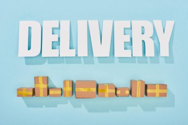 Delivery inscription with shadows near closed cardboard boxes on blue background with copy space stock vector