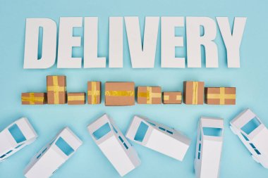 delivery inscription near closed cardboard boxes and mini vans on blue background